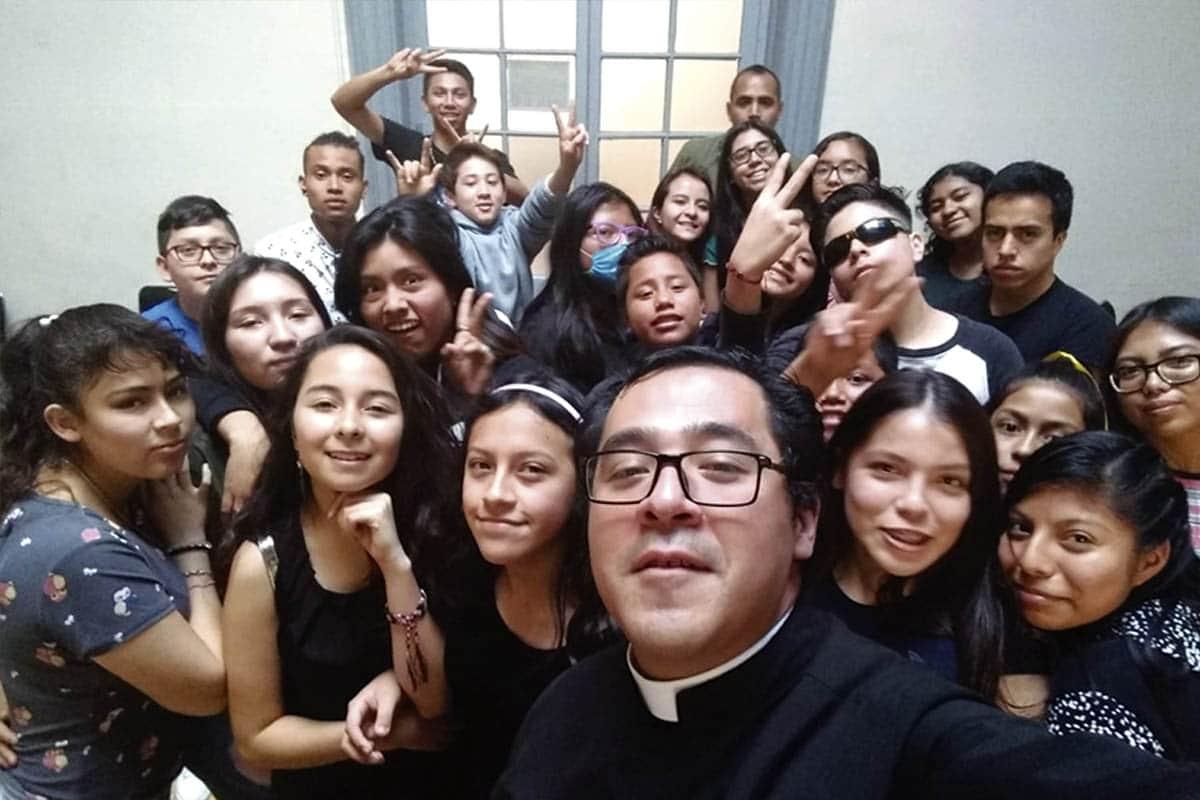 El padre Carlos Alcázar con jóvenes de la catequesis presacramental.