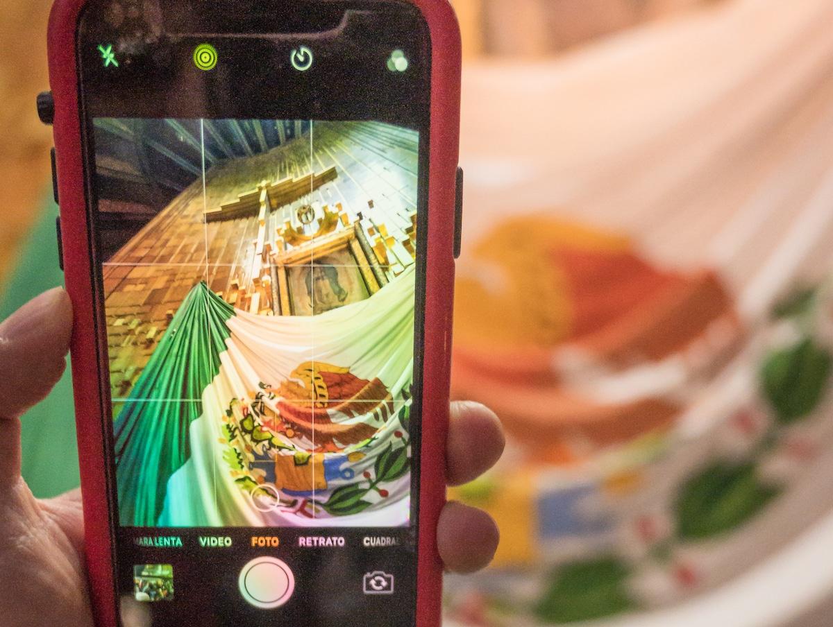 Un fiel toma una fotografía de la imagen de la Virgen de Guadalupe. Foto: Gustavo Rojas