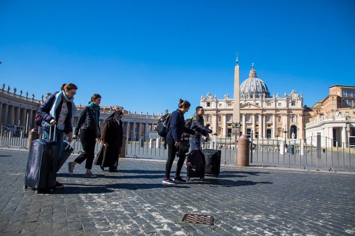 Personas con maletas cruzan la Plaza de San Pedro, en el Vaticano. Foto: Pablo Esparza