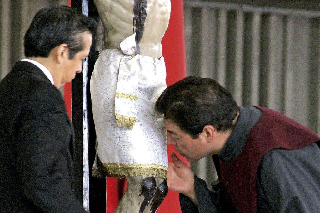 Fieles se acercan a besar los pies de una imagen de Jesús en la cruz.