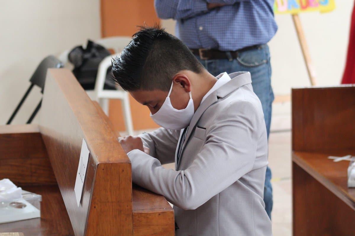 Un niño reza en su Primera Comunión siguiendo las medidas de seguridad. Foto: Miguel Ávila/Parroquia San Pedro Mártir de Verona