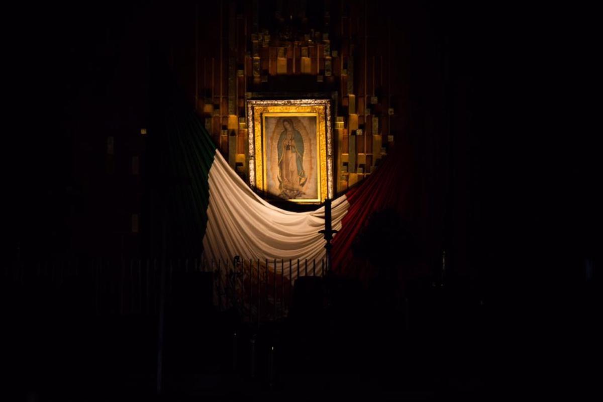 Por la rendija de la puerta cerrada de la Basílica, se asoma la imagen de la Virgen de Guadalupe en la penumbra. Foto: María Langarica