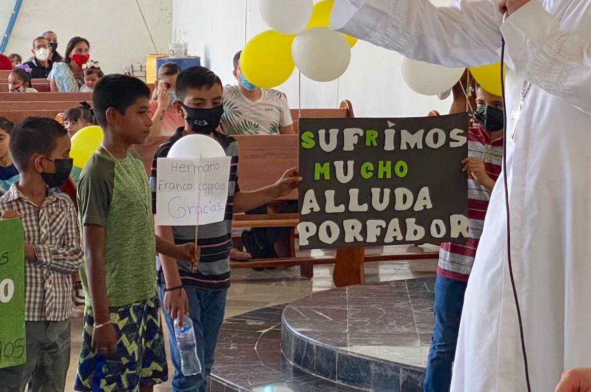 La comunidad recibe con letreros a Mons. Franco Coppola en el Aguaje. Foto: Diócesis de Apatzingán