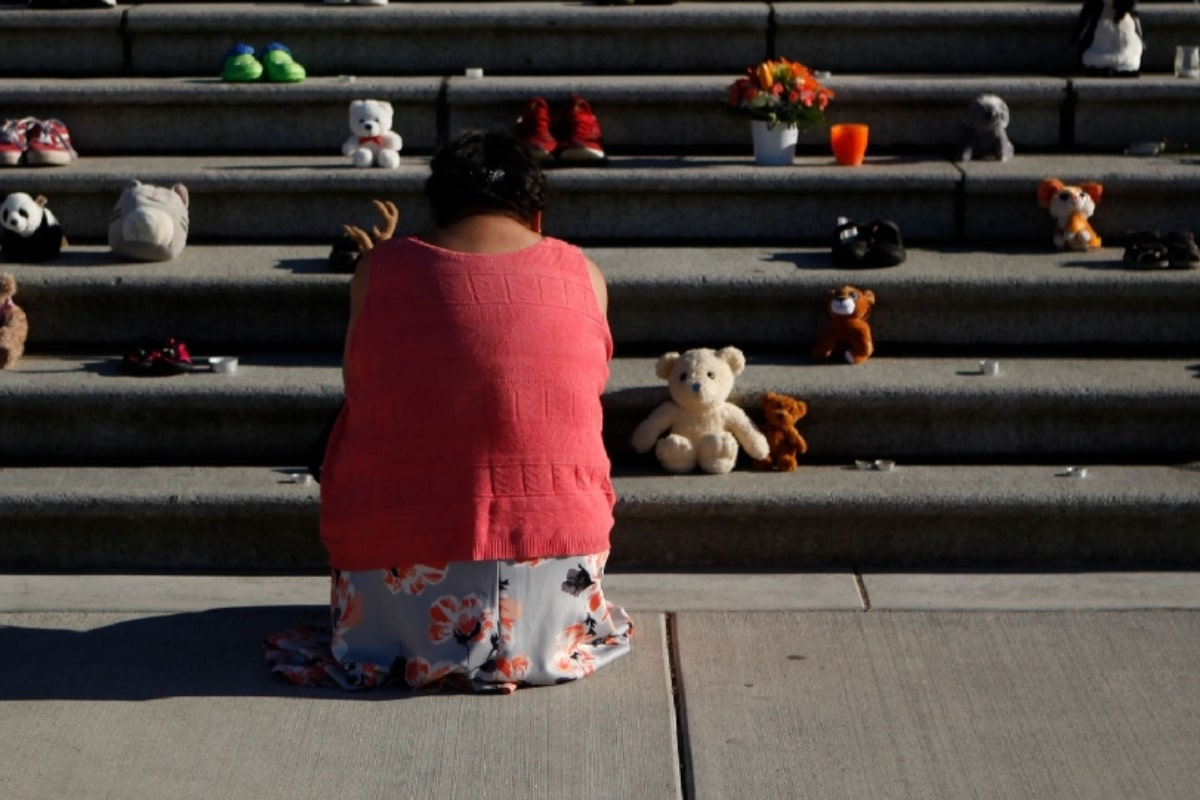 Una mujer miembro de los pueblos originarios de Canadá ante una ofrenda colocada afuera del Congreso de Victoria en honor de los niños fallecidos hallados en tumbas sin nombre. Foto: The Canadian Press.